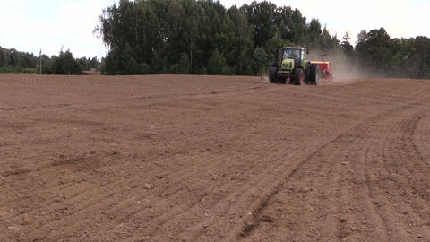 Tractor spread fertilizer on cultivated field in summer Footage