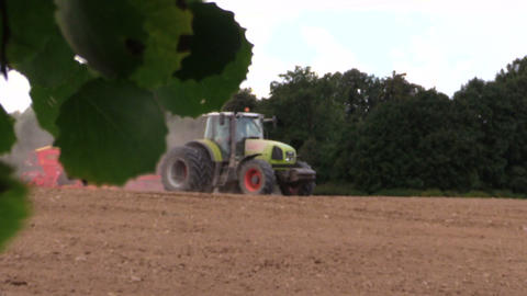 tractor spread fertilizer sow field. Tree leaves move Footage