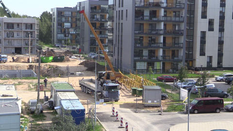 Crane unloads block from truck trailer in construction site Footage