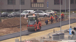 Workers and asphalt paver roller press road near flat house Footage