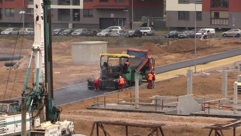 Workers spread hot asphalt on road in residential house district Footage