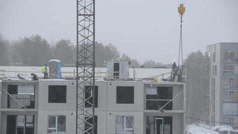 Construction site workers build house. Snow falling Footage