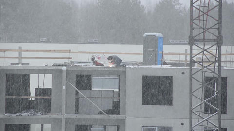 Blizzard snow fall and welder work in outdoor construction site Footage