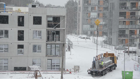 Crane Lift Block House Part And Workers Work In Heavy Blizzard stock footage