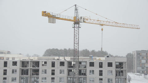 Crane lift block house part and builders work in heavy snow fall Footage