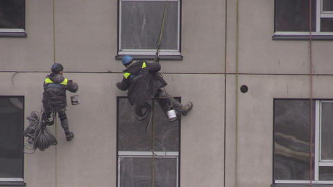 builders climbers work hanging with rope on house wall Footage