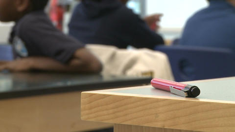 A pen on the corner of a desk with students in the background Footage
