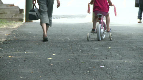 Mother walking along side child on bike with training wheels Footage