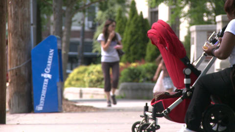 Woman with stroller sitting on sidewalk bench Live Action