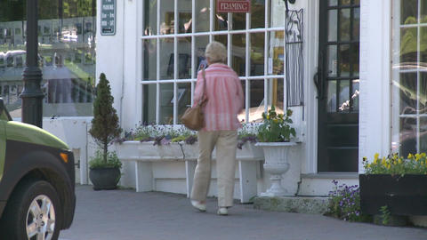 Woman walking in front of store with paned windows and window boxes Footage