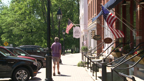 Man walking in front of stores with American Flags Footage