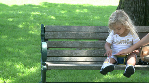 Little girl sitting on park bench Live Action