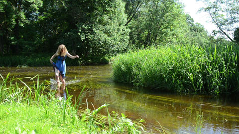 long hair girl wade through creek holds long summer floral dress Live Action