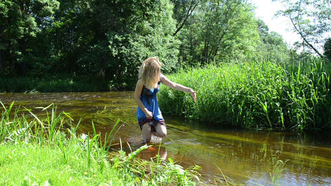 lady palm wipe through the water pulls long grass and goes Footage