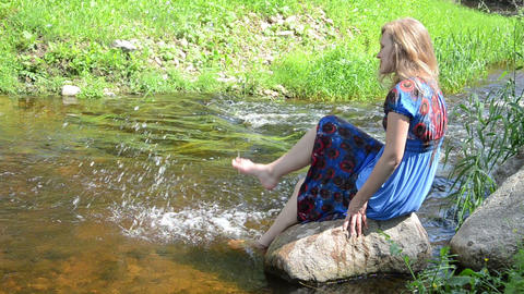 girl sitting big rock with foot splash spray stream water smiles Footage