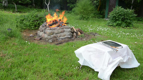fireplace burning bush blowing breeze whip tablecloth on table Footage