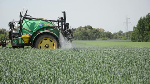 tractor pulls tank with fertilizer from the sprinkler spray crop Footage