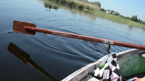 woman rowing with old oar in the water formed ripples Footage