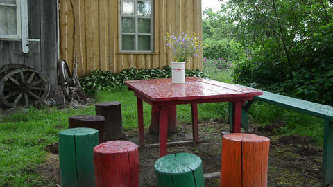 colorfully painted stumps chairs table with vase flowers in rain Footage
