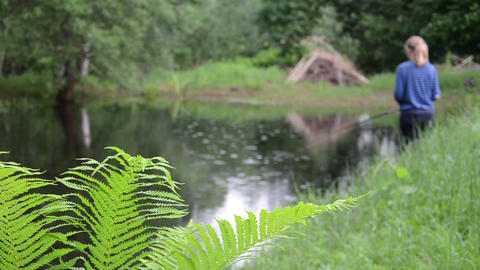 green fern leaves in background to pond stands girl fishing rod Footage