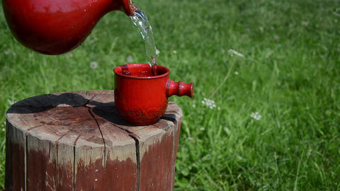 jug with red cup on stump water from cup running over the top Live Action