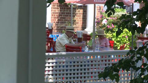 Eating at a sidewalk cafe, under umbrellas. (2 of 2) Footage