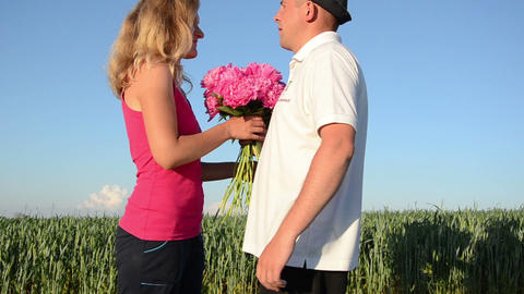 rural guy meets young countrywoman handed large bouquet embraced Footage