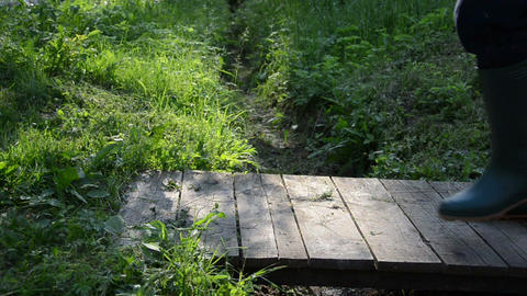 wooden bridge across the ditch goes man with green rubber boots Footage