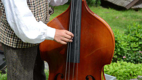 Folk artist in national cloth hand fingers play with contrabass Footage