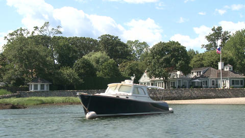 A large home on the water, with a boat docked out front Footage