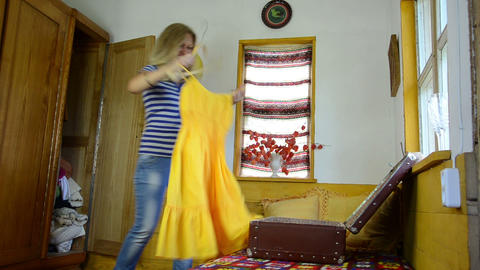 girl takes out of the closet yellow dress takes off hangers Footage