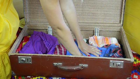 blue long dress is bundled in brown antique suitcase Footage