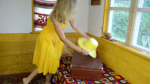 rural room on bed lie large suitcase girl takes yellow hat Footage
