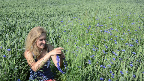 Happy woman sit in wheats cornflowers and put crown on head Footage