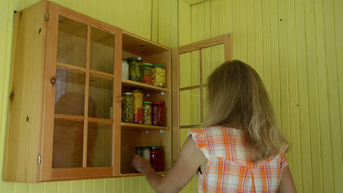 Girl put glass pots full of canned pickled food product to shelf Footage