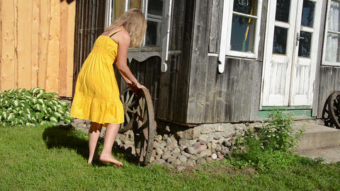 girl in yellow dress rolls old carriage wheel near rural house Footage