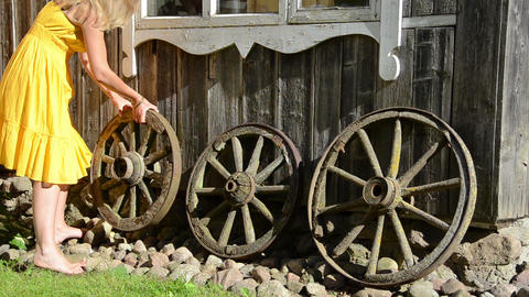 woman adjust old cart wheels decorations near rural house Footage