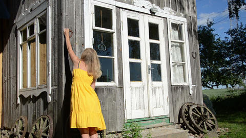 Woman in yellow dress hammering horse shoe on country house wall Footage