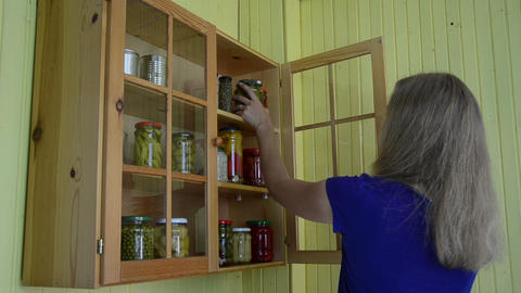 Girl take jar with pickled cucumber vegetable preserve from rack Footage
