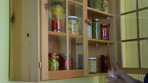 hand open wooden cupboards door puts jar canned garlic Footage