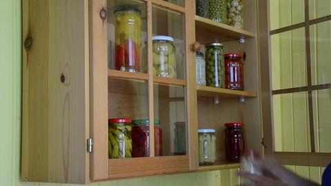 hand open wooden cupboards door puts jar canned garlic Footage