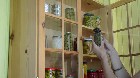 girl from cupboards with glass takes two jars with capers garlic Footage