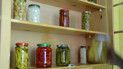 woman puts jars pickled red peppers tomatoes in cupboard shelves Footage