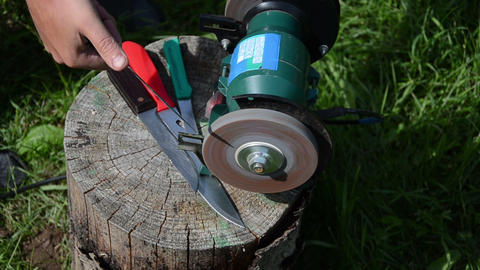 Hand sharpening knives with electric grinder tool on wood log Footage