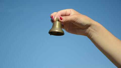 Woman hand with red nails shake small iron bell on blue sky Footage