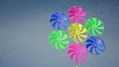 Colorful plastic wind mills spin in wind on background of sky Footage