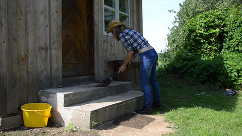 Cowgirl in sweep stairs with wooden broom in rural homestead Footage