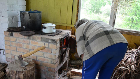 senior woman prepare food put firewood in rural kitchen stove Footage