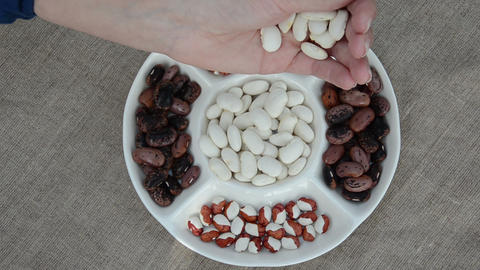 handful flowing in plate white beans next to colored beans Footage
