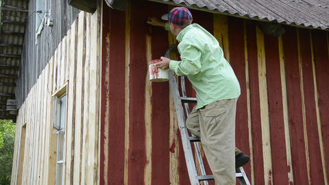 worker climb ladder to the wall paint wooden wall with red paint Live Action